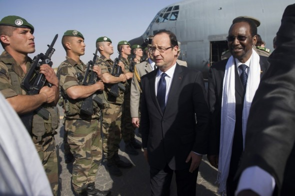 French president Francois Hollande welcomed by his appointed counterpart Dioncounda Traore in Bamako, guarded by the French armed forces.